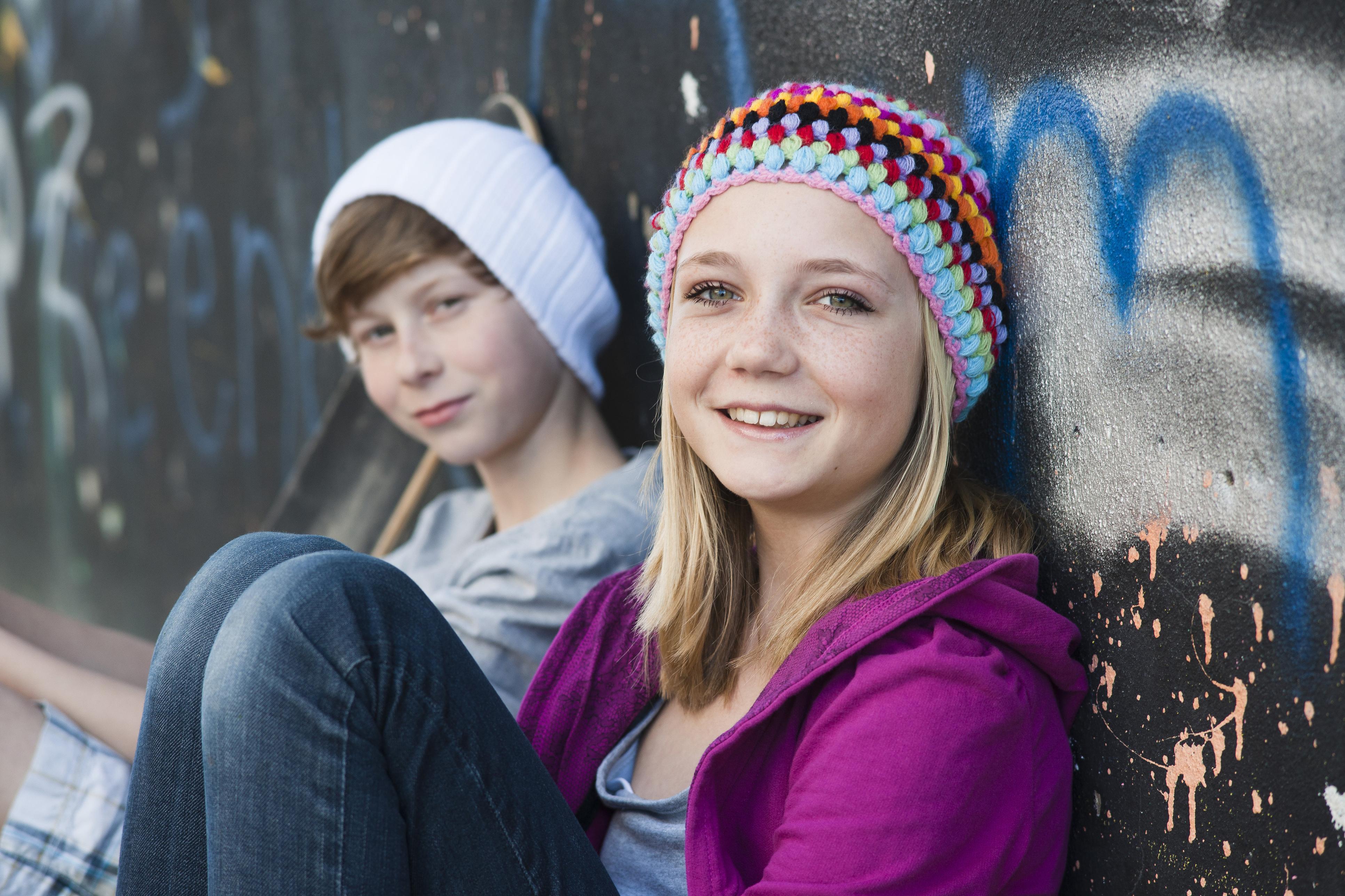 Illustrassjonsbilde, Jente og gutt, ca 12 år, sitter inntil vegg med graffiti, smiler og ser i kamera.