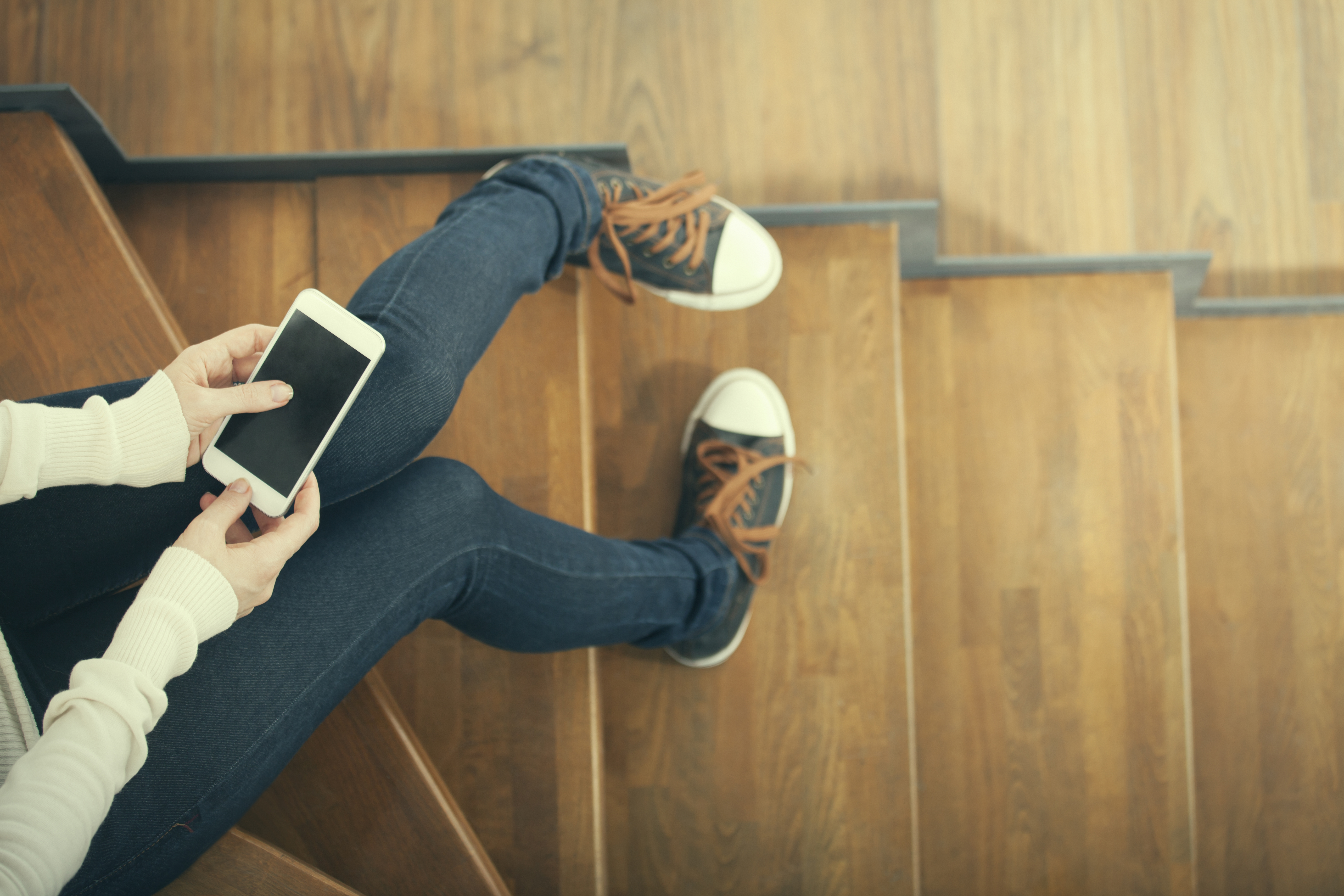 Illustrasjonsbilde, ungdom sitter og trykker på smarttelefon.